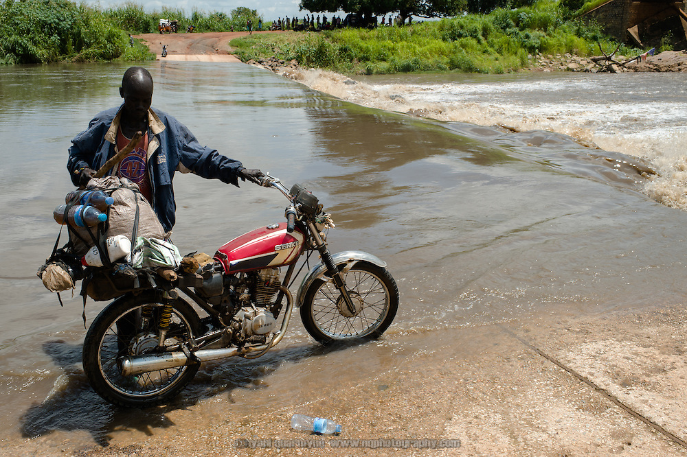His journey interrupted, a man repositions his motorcycle after washing it while waiting for the flooded Lurit River to subside near Juba in Central Equatoria, South Sudan on 6 August 2014.  During the rainy season many parts of the country become impassable. At this river crossing, there were families who had been waiting to cross for two days.