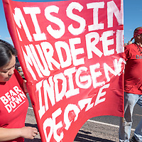 Quixauna Shepherd, left, and Damon Smith, right, carry a red sign south on Indian Route 12 during the Missing and Murdered Indigenous Women and Girls Walk in Window Rock Friday.