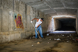Volunteer Kai Frett, cleans the tunnel beneath the Enid Baa Library that leads to waterfront ahead of Tropical Storm Danny.  Any rubbish and debris in the gut will wash down the tunnel and out to the harbor.  Residents and volunteers clean Savan Gut in  preparation for Tropical Storm Danny as a part of Savan CleanUp Day .  St. Thomas, USVI.  22 August 2015.  © Aisha-Zakiya Boyd