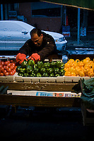 A vendor, first thing on a cold, snowy, winter's morning, setting up produce for sale in Philadelphia's Italian Market.