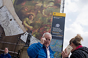 Tourists beneath a giant construction hoarding on Whitehall in Westminster, London.