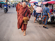 28 JUNE 2014 - DAN SAI, LOEI, THAILAND: Buddhist monks walk through Dan Sai on their morning alms rounds during the Ghost Festival. Phi Ta Khon (also spelled Pee Ta Khon) is the Ghost Festival. Over three days, the town's residents invite protection from Phra U-pakut, the spirit that lives in the Mun River, which runs through Dan Sai. People in the town and surrounding villages wear costumes made of patchwork and ornate masks and are thought be ghosts who were awoken from the dead when Vessantra Jataka (one of the Buddhas) came out of the forest.    PHOTO BY JACK KURTZ