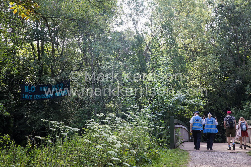 Denham, UK. 26 June, 2020. Metropolitan Police liaison officers walk across a bridge close to a camp created by activists from HS2 Rebellion and Extinction Rebellion UK taking part in a 'Rebel Trail' hike along the route of the HS2 high-speed rail link from Birmingham to London. The activists, who departed from Birmingham on 20th June and will arrive outside Parliament in London on 27th June, are protesting against the environmental impact of the high-speed rail link and questioning the viability of the £100bn+ project.