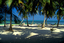 People lounging under palm trees on a tropical beach at Victoria House in Ambergris Caye, Belize.