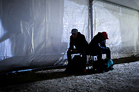 IDOMENI, GREECE - FEBRUARY 10: Two Afghan refugees wait inside a transfer tent set up by the Macedonian border at the Idomeni refugee camp on February 10, 2015 in Idomeni, Greece. Around 50 refugees from Syria, Iraq, Afghanistan are allowed to cross the border to the Former Yugoslav Republic of Macedonia. FYROM's authorities allow refugees to cross the border with the condition that Greek authorities clearly document the refugees' country of final destination. Photo: © Omar Havana. All Rights Are Reserved