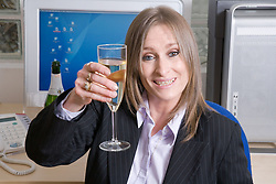 Business woman celebrating with a glass of champagne as she has just secured a successful deal,