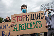 """A protester holds a banner reading """"Stop Killing Afghans"""" as people take part in a demonstration in front the Reichstag  building, seat of the German lower house of Parliament, the Bundestag in Berlin, Germany, August 17, 2021. About 1000 people gathered in front of the  under the call """"Airlift now! Create safe escape routes from Afghanistan!"""", the spontaneous event was organized by Seebrücke and several other human-rights organizations."""