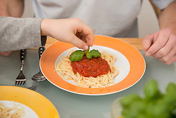 Son decorating father's plate with spaghetti