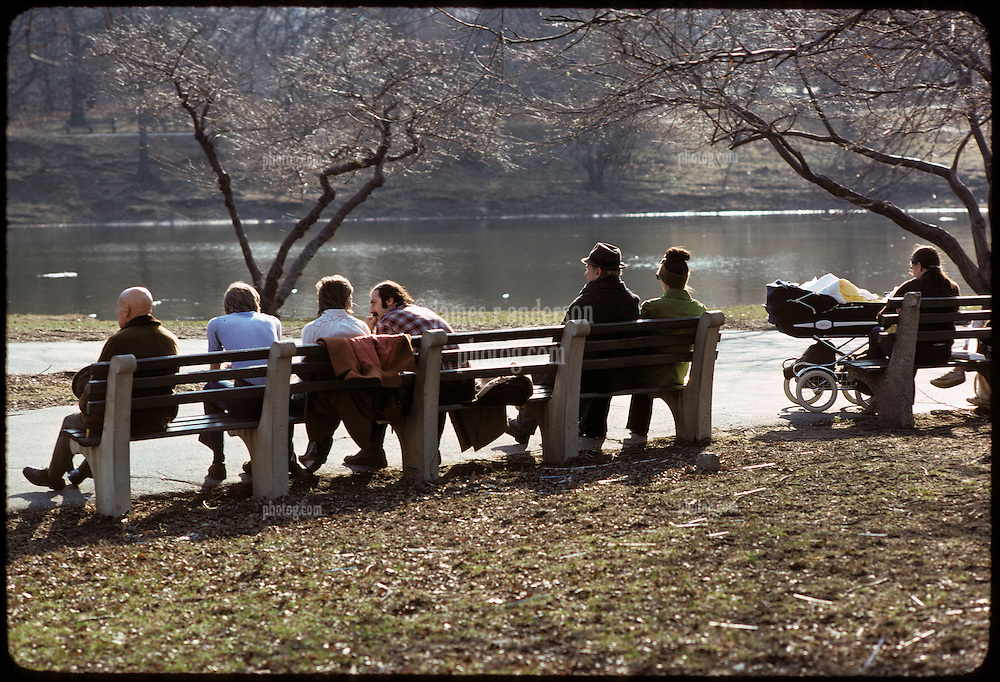 Folk relaxing on a Central Park Bench on a Cold Day with Lake in background, Brown Leaves on the Ground and Bare Trees. A cross section of people sitting, talking and relaxing. Baby Carriage in shot. New York City, February 25, 1976