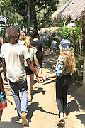 """Friends walking hand in hand through the campus<br /><br />The Green School (Bali) is one of a kind in Indonesia. It is a private, kindergarten to secondary International school located along the Ayung River near Ubud, Bali, Indonesia. The school buildings are of ecologically-sustainable design made primarily of bamboo, also using local grass and mud walls. There are over 600 students coming from over 40 countries with a percentage of scholarships for local Indonesian students.<br /><br />The impressive three-domed """"Heart of School Building"""" is 60 metres long and uses 2500 bamboo poles. The school also utilizes renewable building materials for some of its other needs, and almost everything, even the desks, chairs, some of the clothes and football goal posts are made of bamboo.<br /><br />The educational focus is on ecological sustainability. Subjects taught include English, mathematics and science, including ecology, the environment and sustainability, as well as the creative arts, global perspectives and environmental management. This educational establishment is unlike other international schools in Indonesia. <br /><br />Renewable energy sources, including solar power and hydroelectric vortex, provide over 50% of the energy needs of the school. The school has an organic permaculture system and prepares students to become stewards of the environment. <br /><br />The school was founded by John and Cynthia Hardy in 2008."""