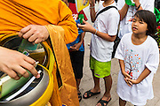 "23 APRIL 2013 - BANGKOK, THAILAND:  A Thai girl watches a monk collects books for literacy projects during the opening ceremony to mark Bangkok as the World Book Capital City 2013. UNESCO awarded Bangkok the title. Bangkok is the 13th city to assume the title of ""World Book Capital"", taking over from Yerevan, Armenia. Bangkok Governor Suhumbhand Paribatra announced plans that the Bangkok Metropolitan Administration (BMA) intends to encourage reading among Thais. The BMA runs 37 public libraries in the city and has modernised 14 of them. It plans to build 10 more public libraries every year. Port Harcourt, Nigeria will be the next World Book Capital in 2014. .PHOTO BY JACK KURTZ"