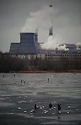 Ulyanovsk, Urals Region, central  Russia, 1994..Unmployed men fish on a frozen lake beside a city factory. The birthplace of Vladiimr Lenin, founder of the Soviet Union, remains true to his Communist ideals. There is little private ownership, and all city industry and local agriculture is controlled by the state..