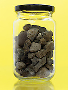 jar against yellow background with stones.