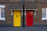 The architecture of neighbouring yellow and red painted front doors seen from the exteriors of Victorian cottages, on 28th November 2016, at Winchester Cottages on Copperfield Street, in the south London borough of Southwark, England.