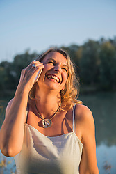 Cheerful woman laughing while talking on smart phone at riverbank, Bavaria, Germany