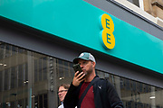 A man having a conversation on his mobile phone passes by a high street branch of EE, or Everything Everywhere, the UKs largest mobile network operator on 2nd September, 2021 in Leeds, United Kingdom. EE is the UKs largest mobile network operator with over 27 million subscribers.