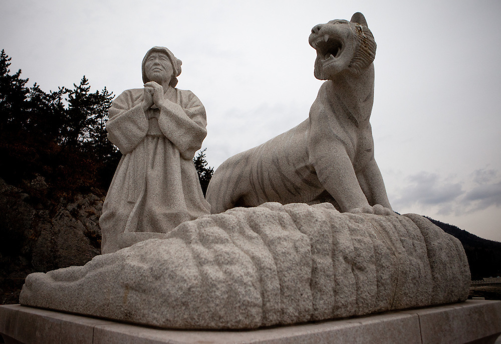 """Monument in Hoedong (Jindo island) showing praying grandmother """"Old Lady Pong"""" and a tiger related to the Jindo myth. Jindo is the 3rd biggest island in South Korea located in the South-West end of the country and famous for the """"Mysterious Sea Route"""" or """"Moses Miracle"""" which is happening during full moon in spring."""