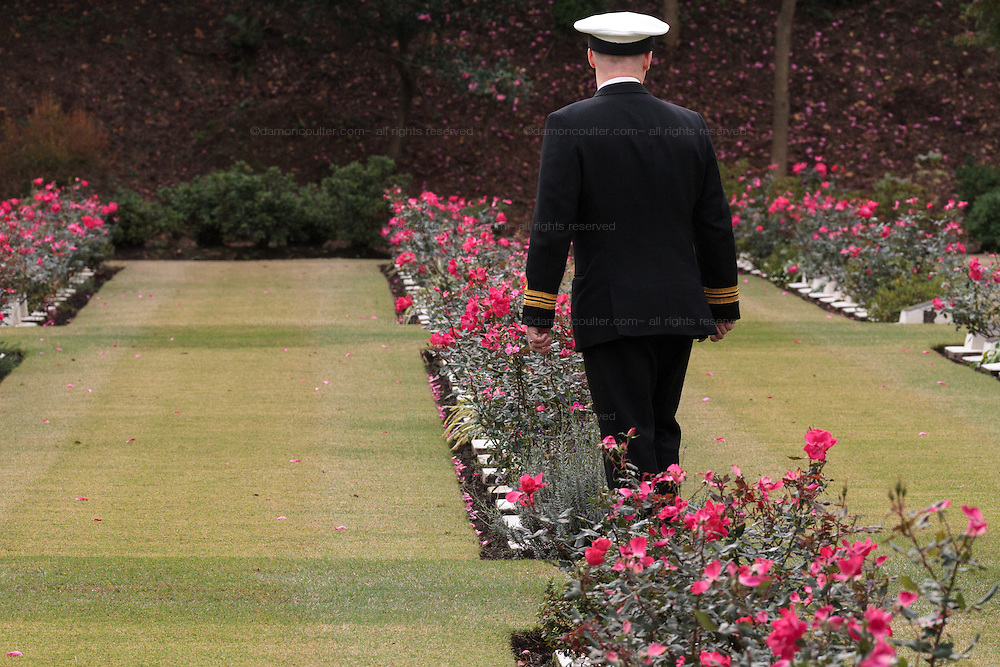 A man in naval uniform looks at graves during the Remembrance Day ceremonies at the Commonwealth War Cemetery in Hodogaya, Yokohama, Japan. Wednesday November 11th 2015