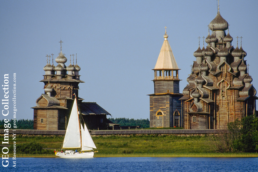 A boat  sails by Intercession Church and Transfiguration Cathedral.