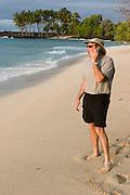 Phillip Greenspun talking on his cellphone on Pu'u Kala beach, Big Island of Hawaii. MODEL RELEASED.
