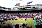 Crowds watch in Centre Court as the Tennis events at the London 2012 Olympics take place at Wimbledon. Serena Williams receives her gold medal during the medal ceremony. At this point the American flag falls down.