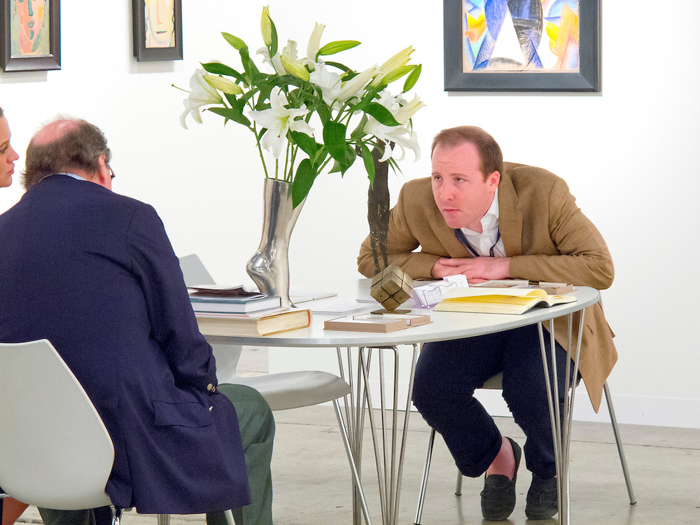 Gallerist and visitors, possibly buyers at Art Basel Miami Beach 2010