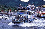 Buses and trucks weighed down with passengers and goods cross a swollen river during the rainy and typhoon season, Philippines