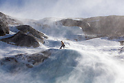 An ice climber is surrounded by blowing snow on a cliff above Black Lake, Rocky Mountain National Park, Colorado.