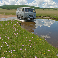 A four-wheel drive van splashes through a stream south of Mongolia's Darhad Valley.  This road washes out regularly in summertime rainstorms that turn it into impassable, boggy mud.