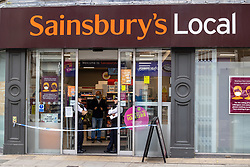 Licensed to London News Pictures. 26/08/202. London, UK. Police guard a Local Sainsbury's supermarket in Fulham, southwest London this morning after a man was arrested for contaminating food with syringes at three supermarkets last night. Tescos, Sainsbury's and a Waitrose on the Fulham Palace Road in London have been closed with forensic teams checking food stocks. Police have urged anyone who bought food on Wednesday evening at one of the stores to dispose of it as soon as possible. Photo credit: Alex Lentati/LNP