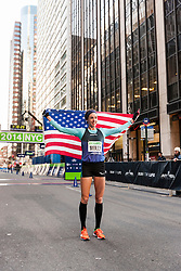Molly Huddle with American flag after finishing race