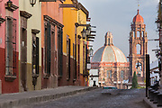 Spanish colonial style homes along the cobblestone Recreo street with the dome of Las Monjas Church dome and spire of the San Francisco Church in the historic center of San Miguel de Allende, Mexico.