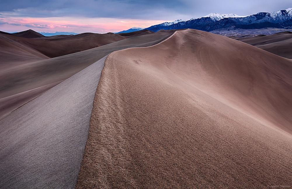 Sunrise paints the meandrous dunes with subtle hues.
