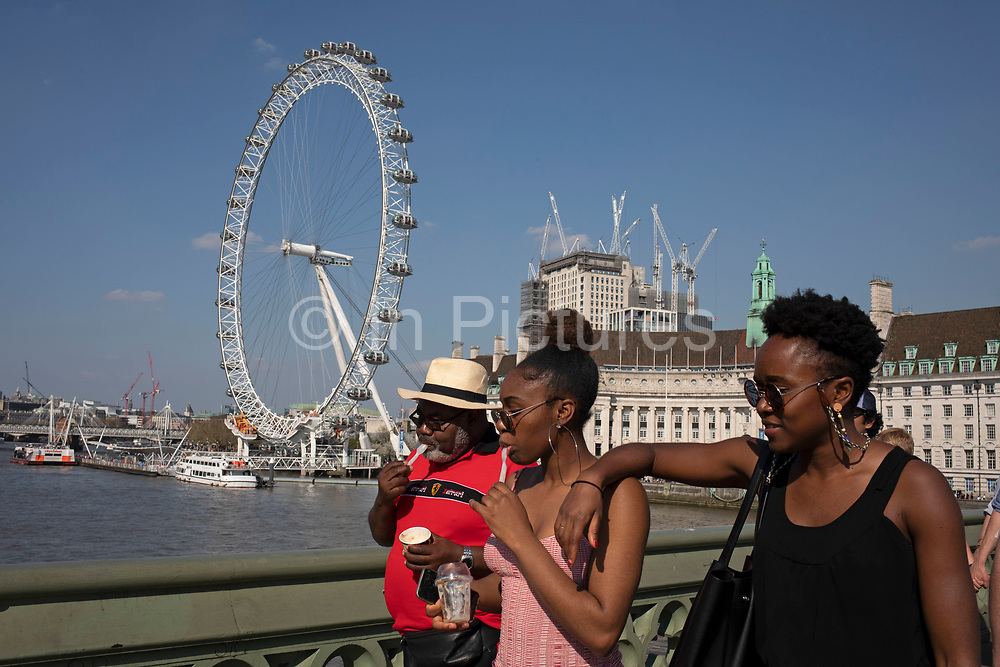 Tourists cross Westminster Bridge by the River Thames at Westminter in London, England, United Kingdom. With the iconic London Eye behind this is one of the busiest areas for tourism in the city.