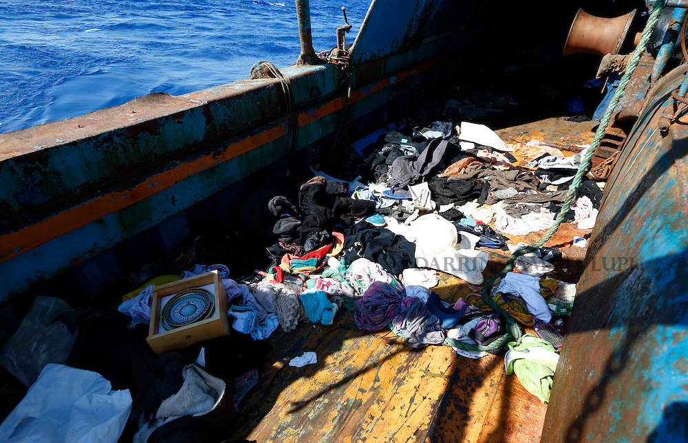 Migrants' belongings and a navigational compass litter the deck of a wooden boat from which migrants were rescued 10.5 miles (16 kilometres) off the coast of Libya August 6, 2015.  An estimated 600 migrants on the boat were rescued by the international non-governmental organisations Medecins san Frontiere (MSF) and the Migrant Offshore Aid Station (MOAS) without loss of life on Thursday afternoon, according to MSF and MOAS, a day after more than 200 migrants are feared to have drowned in the latest Mediterranean boat tragedy after rescuers saved over 370 people from a capsized boat thought to be carrying 600.<br /> REUTERS/Darrin Zammit Lupi <br /> MALTA OUT. NO COMMERCIAL OR EDITORIAL SALES IN MALTA