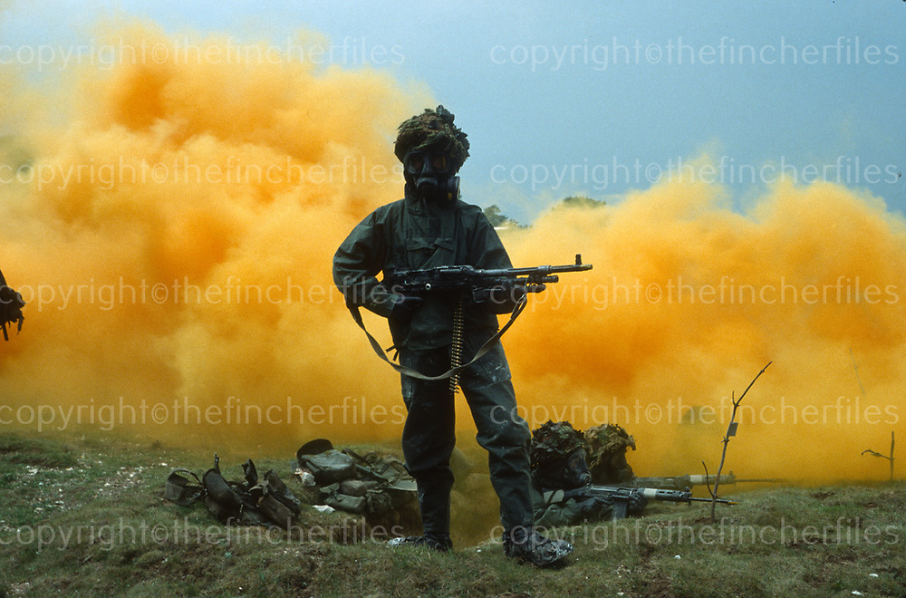 British Army Chemical warfare training at Porton Down, UK in 1980. In the foreground a GMPG machinegunner poses in full NBC kit, in the background his section watch with their L1A1 SLRs at the ready. Photograph by Terry Fincher
