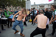 Extinction Rebellion climate change activists dancing as sites around Westminster are blocked on 8th October 2019 in London, England, United Kingdom. Extinction Rebellion is a climate group started in 2018 and has gained a huge following of people committed to peaceful protests. These protests are highlighting that the government is not doing enough to avoid catastrophic climate change and to demand the government take radical action to save the planet.
