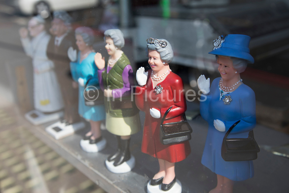 Queen Elizabeth II waving figurines wearing different outfits for sale at a souvenir shop in London, England, United Kingdom.