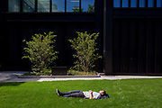 A sleeping man enjoys a moment of quiet solitude on a patch of urban grass in the busy metropolis, on 17th Juy 2017, in the City of London, England.