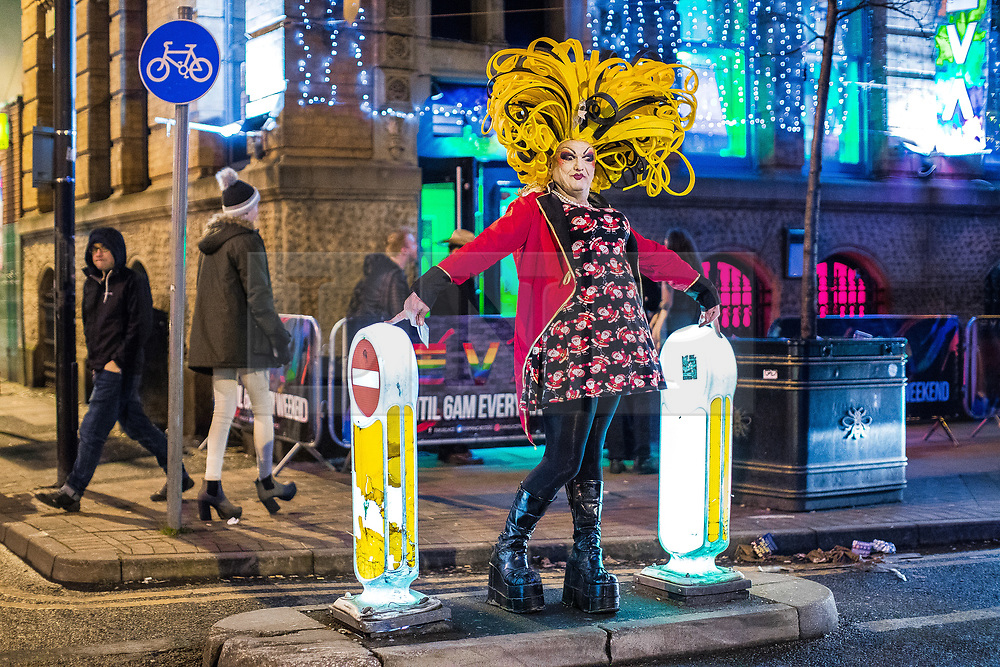 """© Licensed to London News Pictures . 15/12/2017. Manchester, UK. A club promoter wearing drag hands out flyers on Sackville Street in Manchester's """" Gay Village """" . Revellers out in Manchester City Centre overnight during """" Mad Friday """" , named for historically being one of the busiest nights of the year for the emergency services in the UK . Photo credit: Joel Goodman/LNP"""