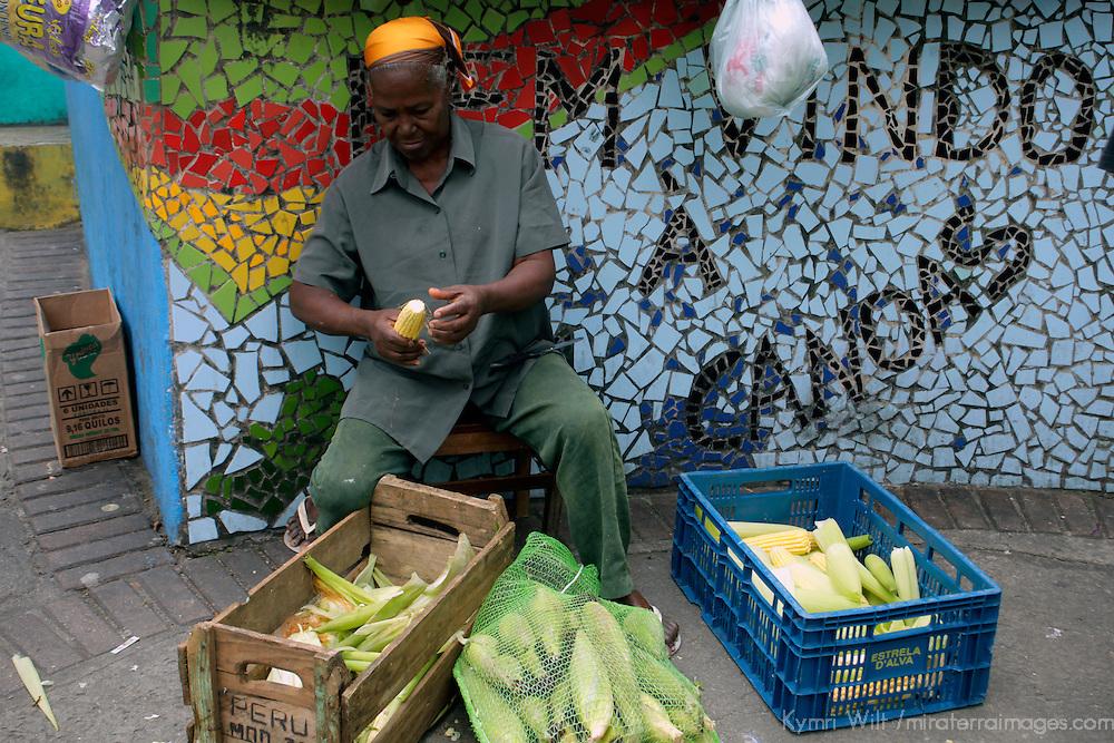 South America, Brazil, Rio de Janeiro. Woman husking corn on corner in Favela of Vila Canoas.