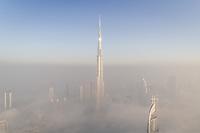 Aerial view of misty Burj Khalifa in Business Bay, Dubai, UAE.
