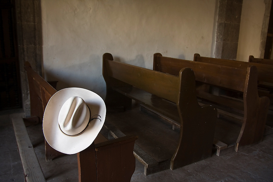 A white cowboy hat rests on a church bench at the entrance of the San Javier Mission in the Sierra de Giganta outside Loreto, Baja California Sur, Mexico. Founded by Jesuits in 1699 and built in the mid 18th century, the church is one of the best preserved of the California missions.