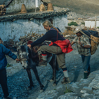 Meredith Wiltsie mounts a horse to ride up 17,769-foot Thorang La pass north of Annapurna in Nepal.