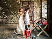 17 MARCH 2015 - BANGKOK, THAILAND: A woman and her fiance get ready for their prewedding photos in the old Customs House in Bangkok. With its evocative architecture and turn of the century mood, the Customs House is a popular setting for wedding photos and portraits. The old Customs House was once the financial gateway to Thailand (before 1932 called Siam). It was designed by an Italian architect in the 1880s. In the 1950s, customs moved to new, more modern building and the Customs House became the headquarters for the Marine firefighters. The firefighters now live in the decrepit buildings with their families.    PHOTO BY JACK KURTZ