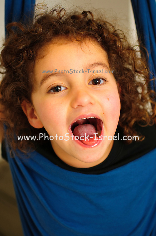 Happy and excited young girl of eight in a hanging sack