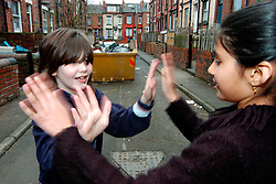 Girls playing on the street Beeston Leeds UK