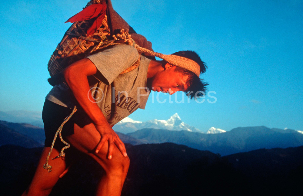 A young Nepali boy is undergoes a recruitment test for the Gurkha Regiment called the Doko race, part of a tough endurance series to find physically perfect specimens for British army infantry training, on 16th January 1997, in Pokhara, Nepal. Carrying 30kg of river stones in a traditional Himalayan doko basket for 3km up foothills within 37 minutes to pass.  60,000 boys aged between 17-22 or 25 for those educated enough to become clerks or communications specialists report to designated recruiting stations in the hills each November, most living from altitudes ranging from 4,000-12,000 feet. After initial selection, 7,000 are accepted for further tests from which 700 are sent down here to Pokhara in the shadow of the Himalayas. Only 160 of the best boys succeed in the journey to the UK. Nepal has been supplying youths for the British army since the Indian Mutiny of 1857.