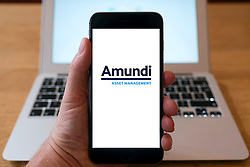 Amundi fund management company logo on smart phone screen.