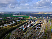 Nederland, Zuid-Holland, Zwijndrecht, 25-02-2020; Kijfhoek, rangeerterrein voor goederentreinen. Overzicht van de verdeelsporen (richting Rotterdam). Kijfhoek huisvest Keyrail, exploitant Betuweroute en is in beheer bij ProRail. De Betuweroute, die begint als Havenspoorlijn op de Maasvlakte, verbindt via Kijfhoek de Rotterdamse haven met het achterland. Het rangeeremplacement dient voor het sorteren van goederenwagons waarbij gebruik gemaakt wordt van de zwaartekracht, het 'heuvelen': de wagons worden de heuvel opgeduwd, bij het de heuvel afrollen komen ze, door middel van wissels, op verschillende verdeelsporen. Railremmen zorgen voor het automatisch remmen van de wagons. Na het heuvelproces staan de nieuw samengestelde treinen op aparte opstelsporen.<br /> Kijfhoek, railway yard (train shunting-yard) used by ProRail and Keyrail (Betuweroute operator). Kijfhoek connects via the Betuweroute (beginning as Havenspoorlijn on the Maasvlakte), through the port of Rotterdam with the hinterland. The shunting yard for sorting wagons makes use of gravity. The new trains are assembled on separate tracks.<br /> luchtfoto (toeslag op standard tarieven);<br /> aerial photo (additional fee required)<br /> copyright © 2020 foto/photo Siebe Swart
